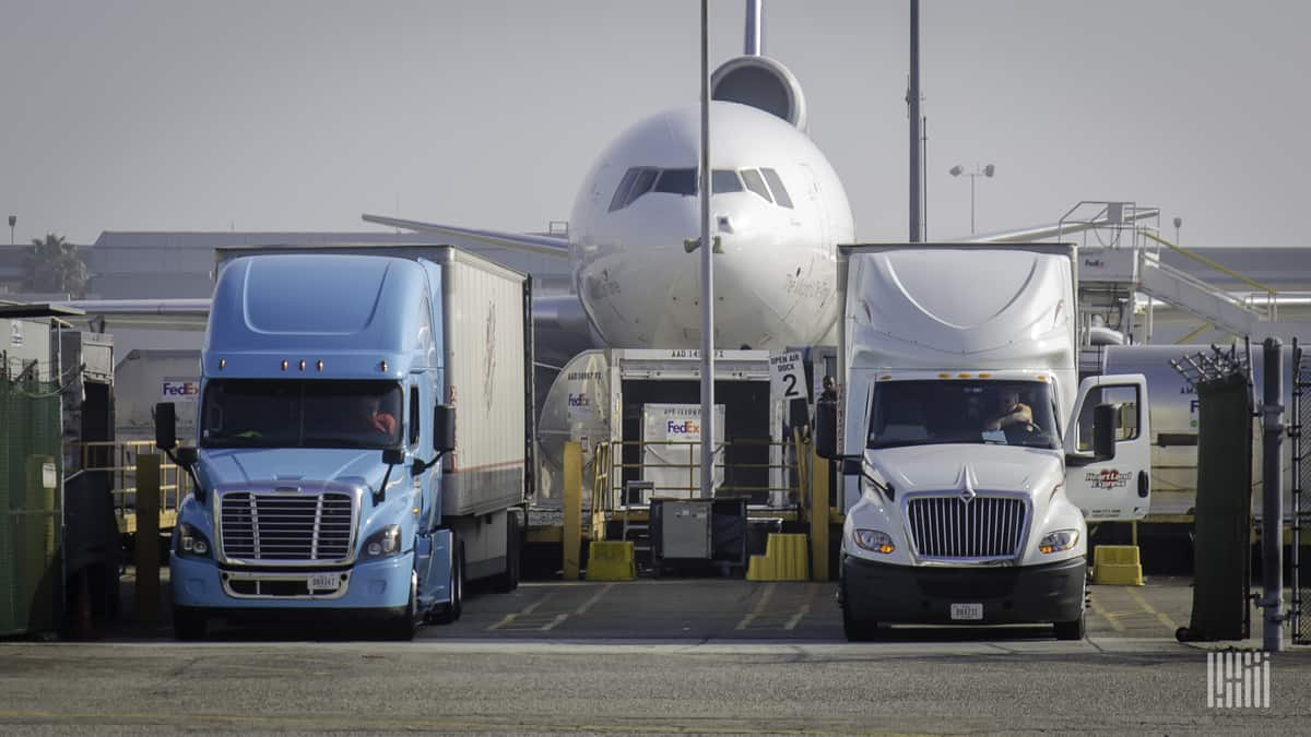 A white FedEx cargo jet flanked by large trucks. The air cargo market is volatile this summer and prices are heading up on key lanes.
