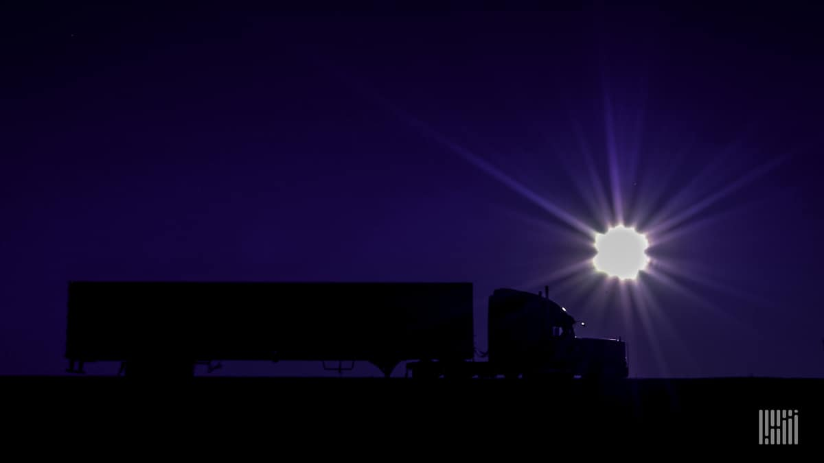 Tractor-trailer heading down highway with bright sun on the dusk/dawn horizon.