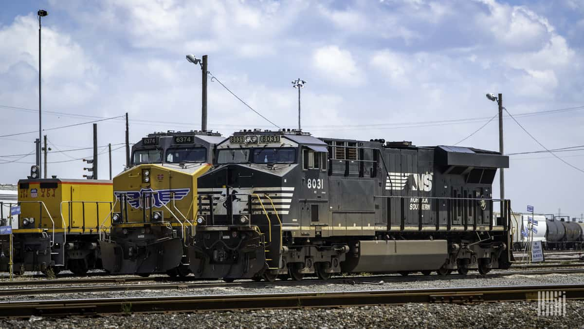 A photograph of a Norfolk Southern locomotive and another freight train locomotive parked at a rail yard.