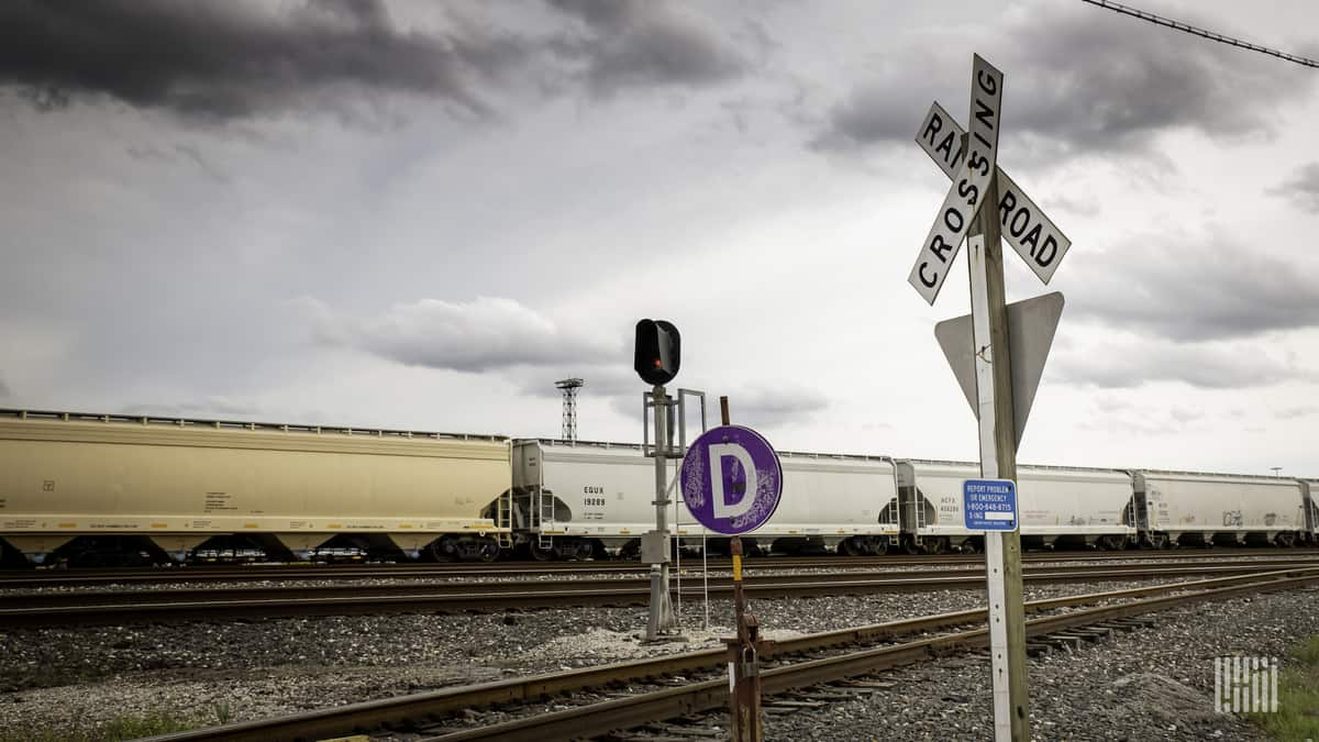 A photograph of a train hauling grain hopper cars. The train is at a railroad crossing.