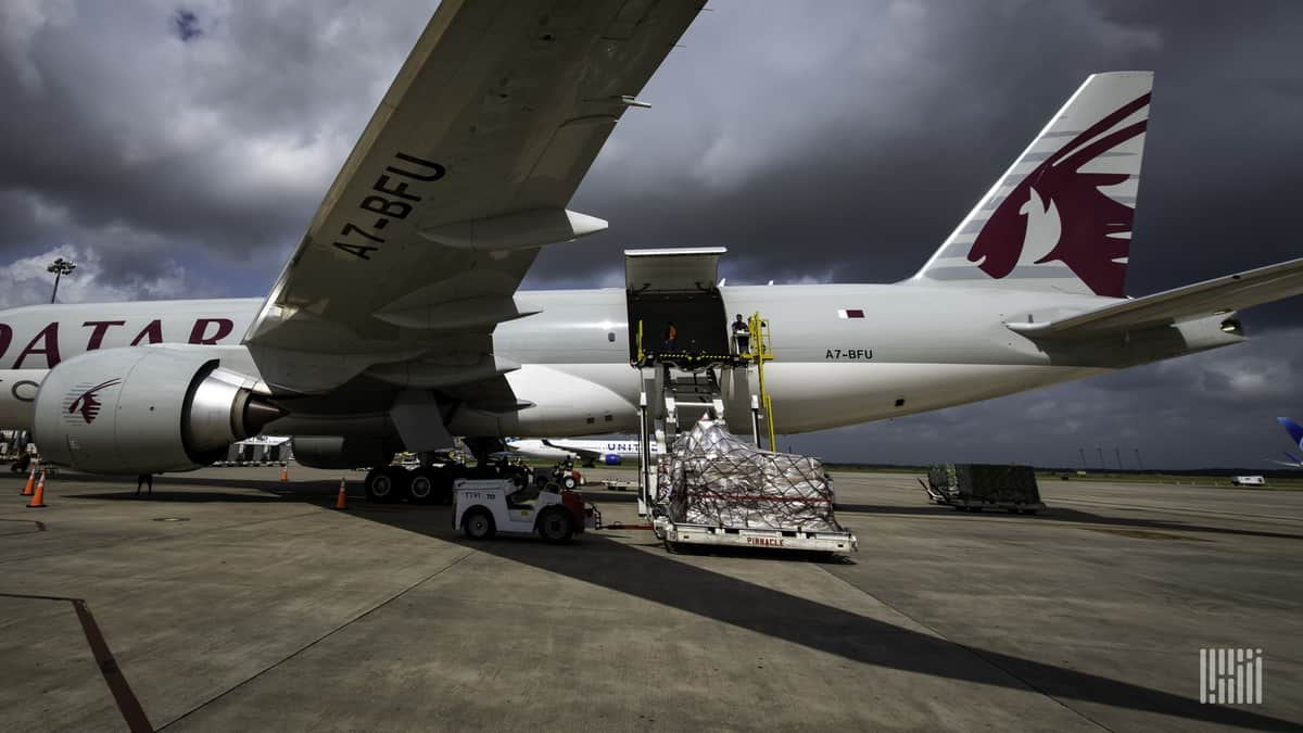 A large jet gets loaded with pallets of cargo under a cloudy sky. Air cargo security rules are tightening in the next year.