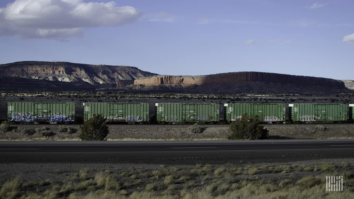 A photograph of a train of boxcars traveling through a desert-like field. There is a mountain range in the background.