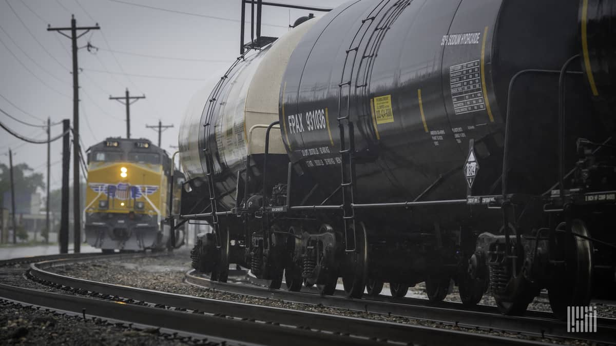 A photograph of a Union Pacific train behind a train of tank cars. They are at a rail yard.