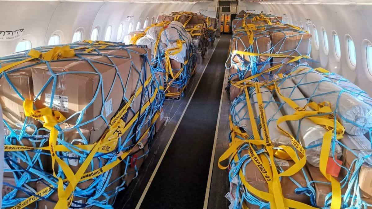 Boxes tied down in the passenger cabin with netting after seats removed. from Scoot jet.