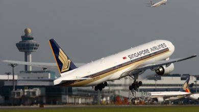 White Singapaore Airlines jetliner with blue tail lifts off from runway with airport control tower in background. Singapore Airlines is helping the World Food Program.