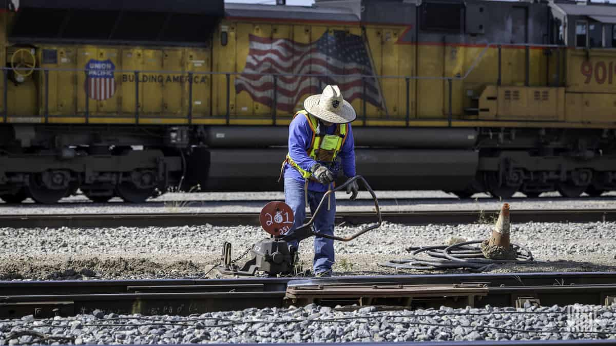 A photograph of a worker fixing track in a rail yard. There is a parked train behind him.