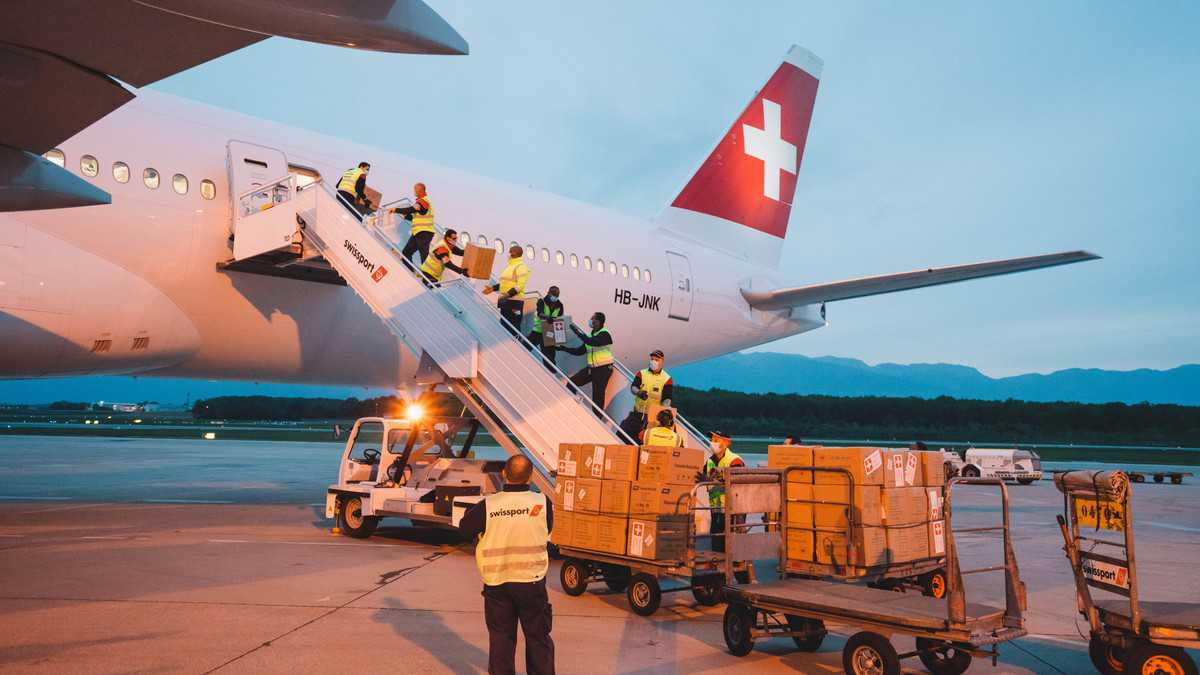 Boxes of PPE being hand-passed up the passenger stairs for loading in cabin of Swiss Air flight. Swiss Air received permission to load all kinds of commodities in the cabin.