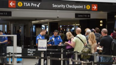 Travelers in line at a TSA airport checkpoint.