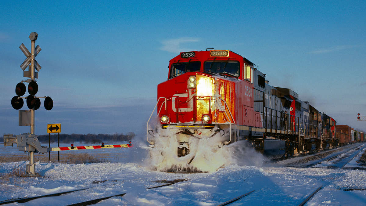 A photograph of a CN train at a rail grade crossing. There is snow on the ground.
