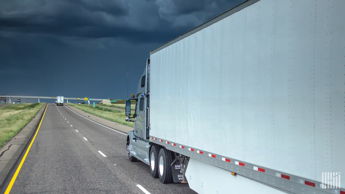 Tractor-trailer heading down highway with dark storm cloud ahead.