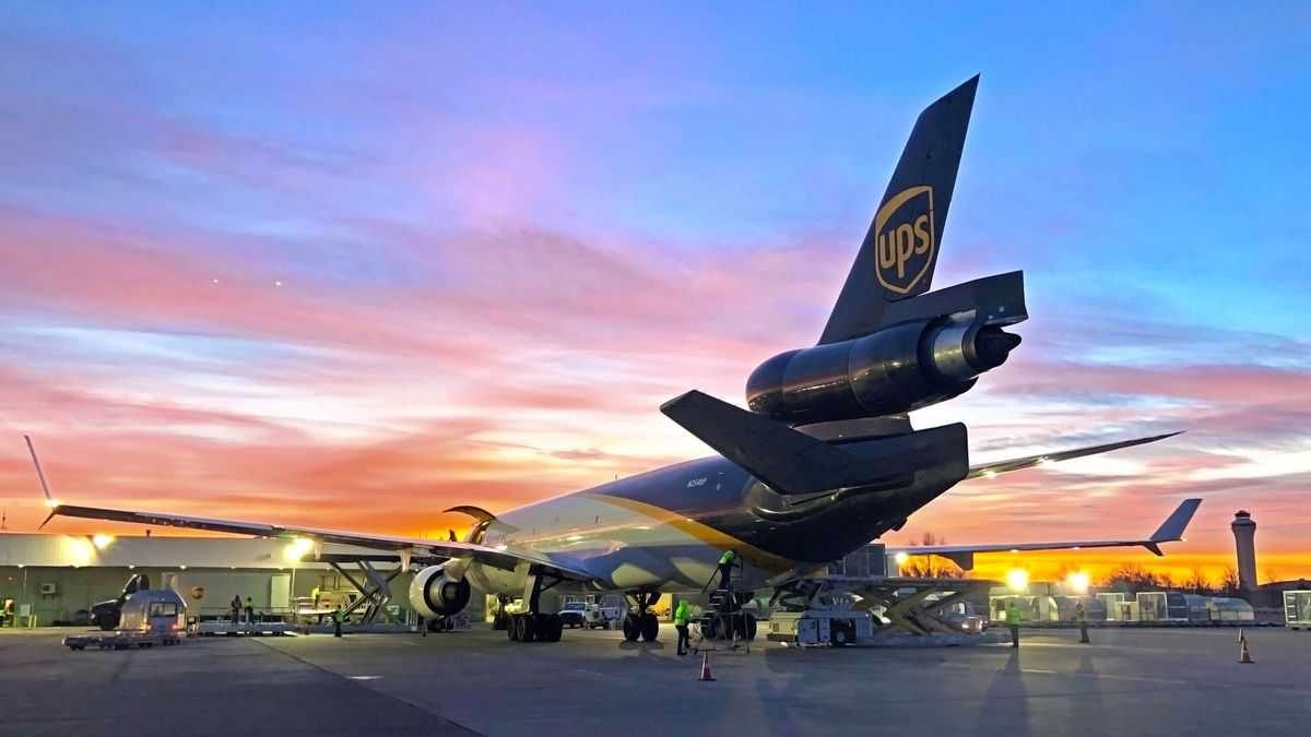 A UPS plane at sunset, view from behind the tail in shadows. UPS is expanding at Kansas City Airport.