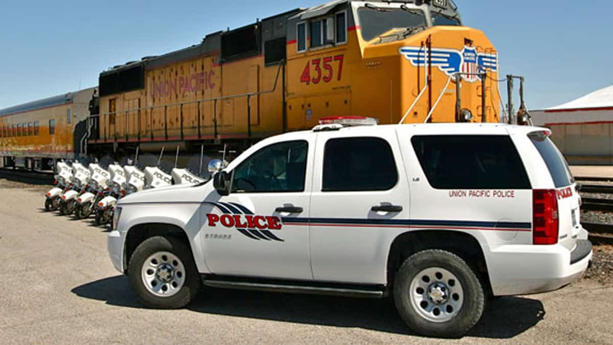 A photograph of a van that says Union Pacific Police on the van. Behind the van is a Union Pacific train.
