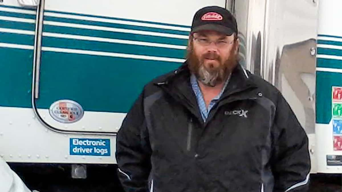 Canadian trucker Jean Pothier standing in front of his truck. He and other Canadian truckers reporting being denied access to medical care unless they self-isolate over COVID-19 fears.