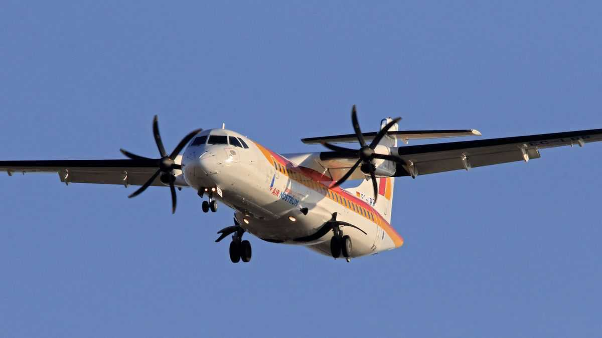 A twin-engine, turboprop plane coming in for landing with wheels retracted. The ATR 72-600 is popular with many regional airlines.