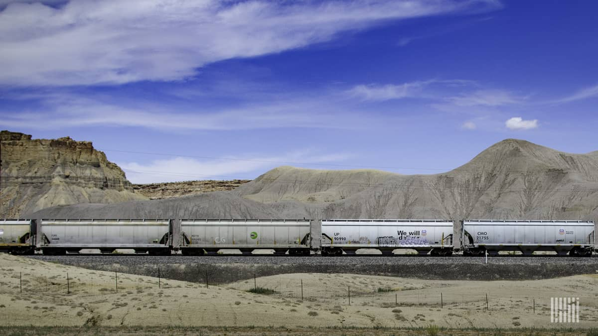A photograph of a train with hoppers. The train is crossing a desert-like landscape.
