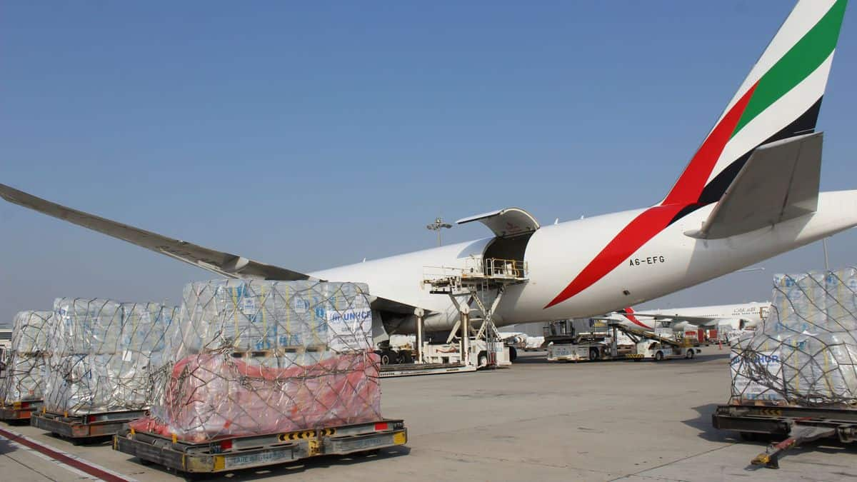 Pallets of humanitarian cargo sit outside next to a big plane waiting to be loaded on a sunny day.