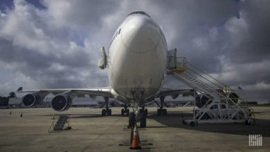 A front-end of jumbo jet looking straight on from nose under sunny sky.