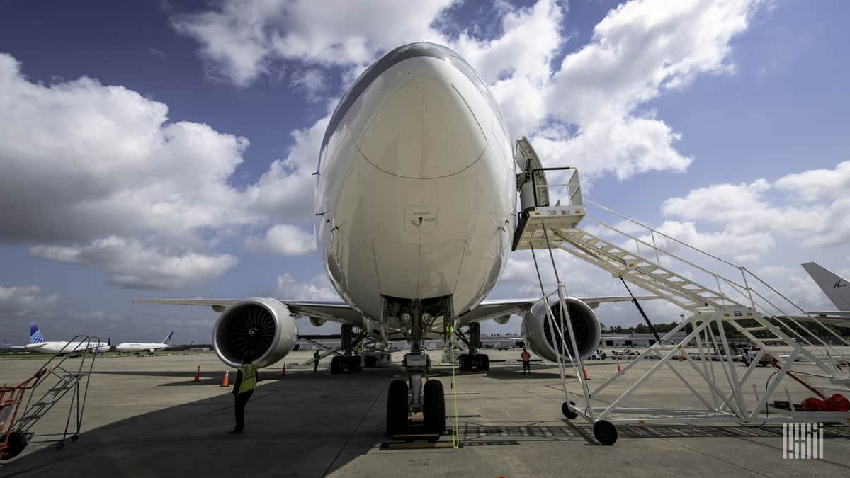 Staring staight at the nose of a 747 cargo jet under a bright sky with white clouds.