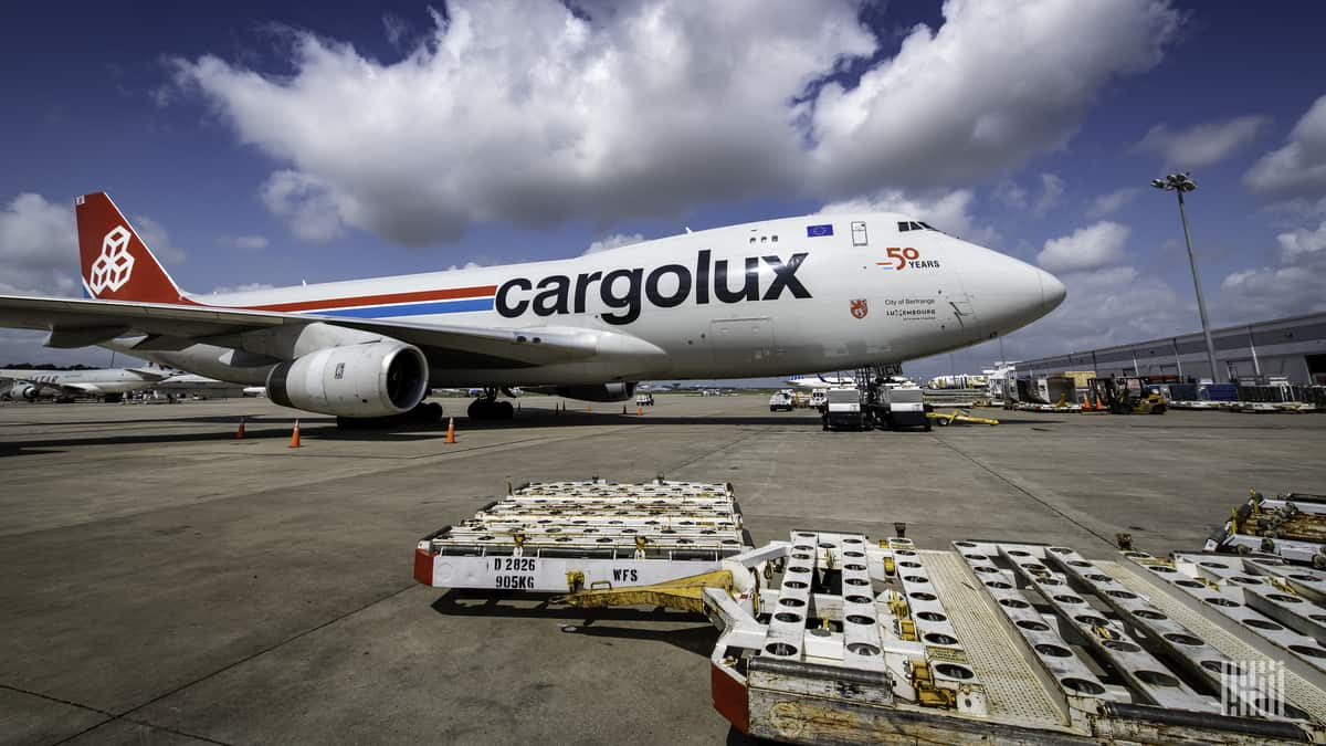 A white cargo jumbo jet with empty pallets on the ground on sunny day. The side of the plane says Cargolux.