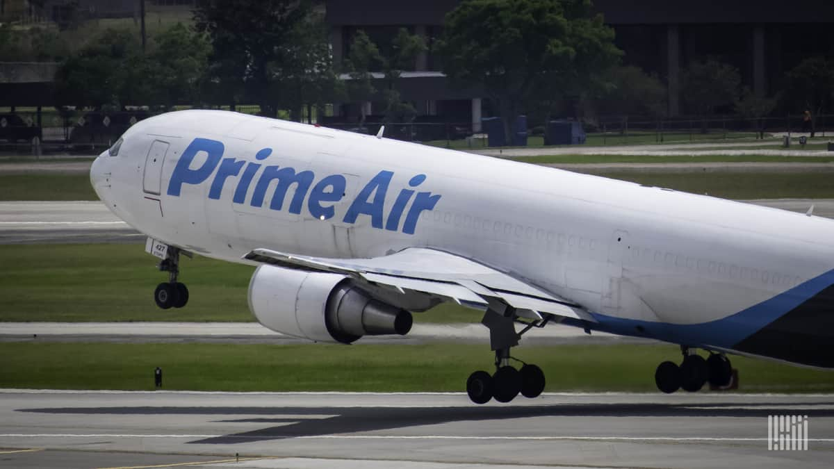 A white Amazon cargo jet with front wheel lifting off on takeoff.