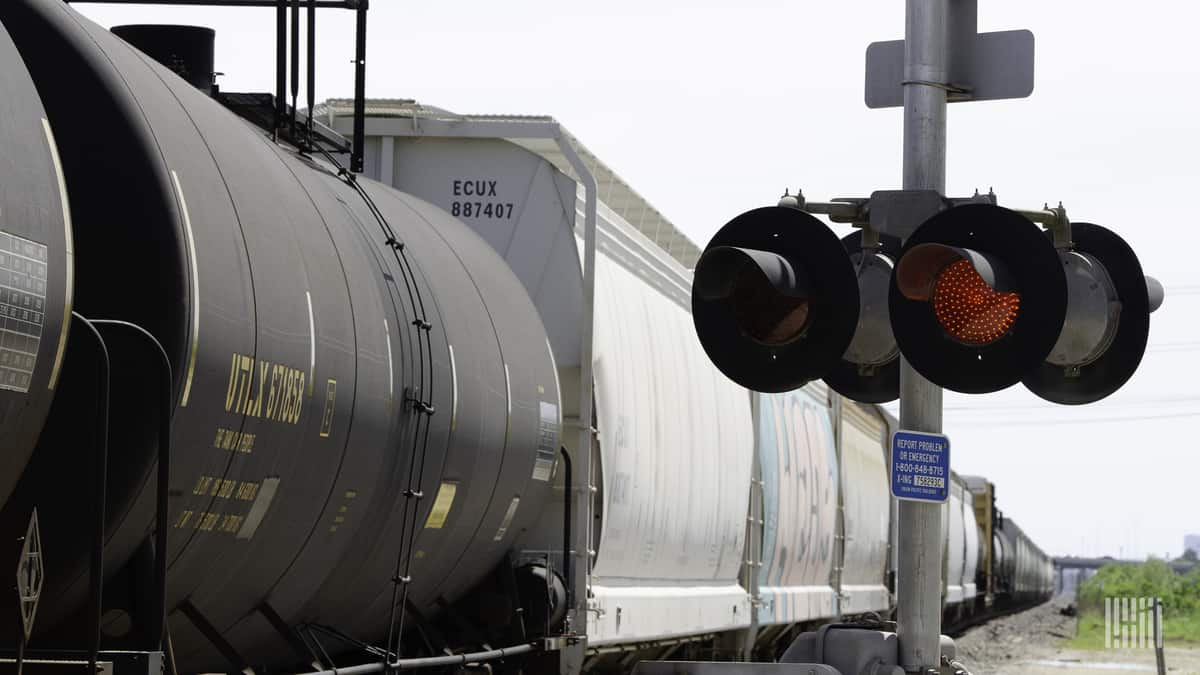 A photograph of a tank car and a hopper traveling by a railroad crossing.