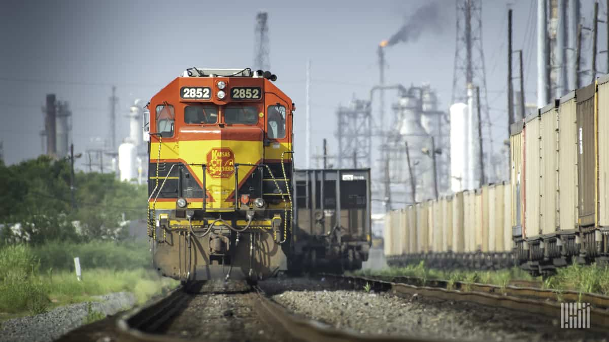 A photograph of a Kansas City Southern train traveling away from a city center.
