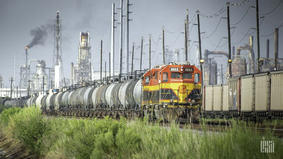 A photograph of a Kansas City Southern train traveling by an industrial yard.