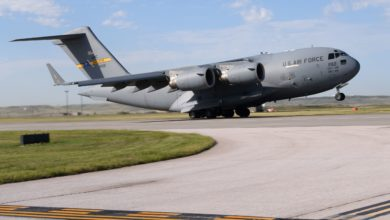 A big gray U.S. Air Force cargo jet takes off. Military planes might be used to delivery COVID vaccines.