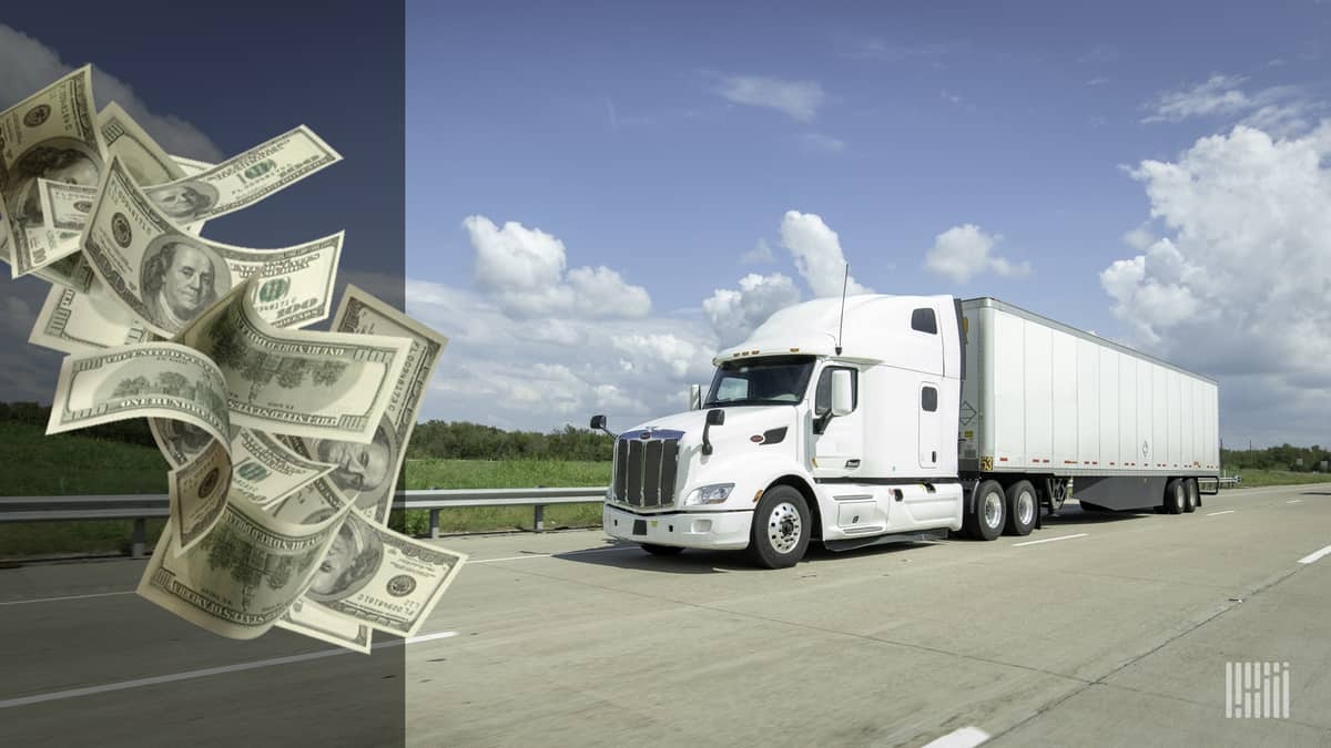 White truck driving down highway with a stack of cash flying to the left