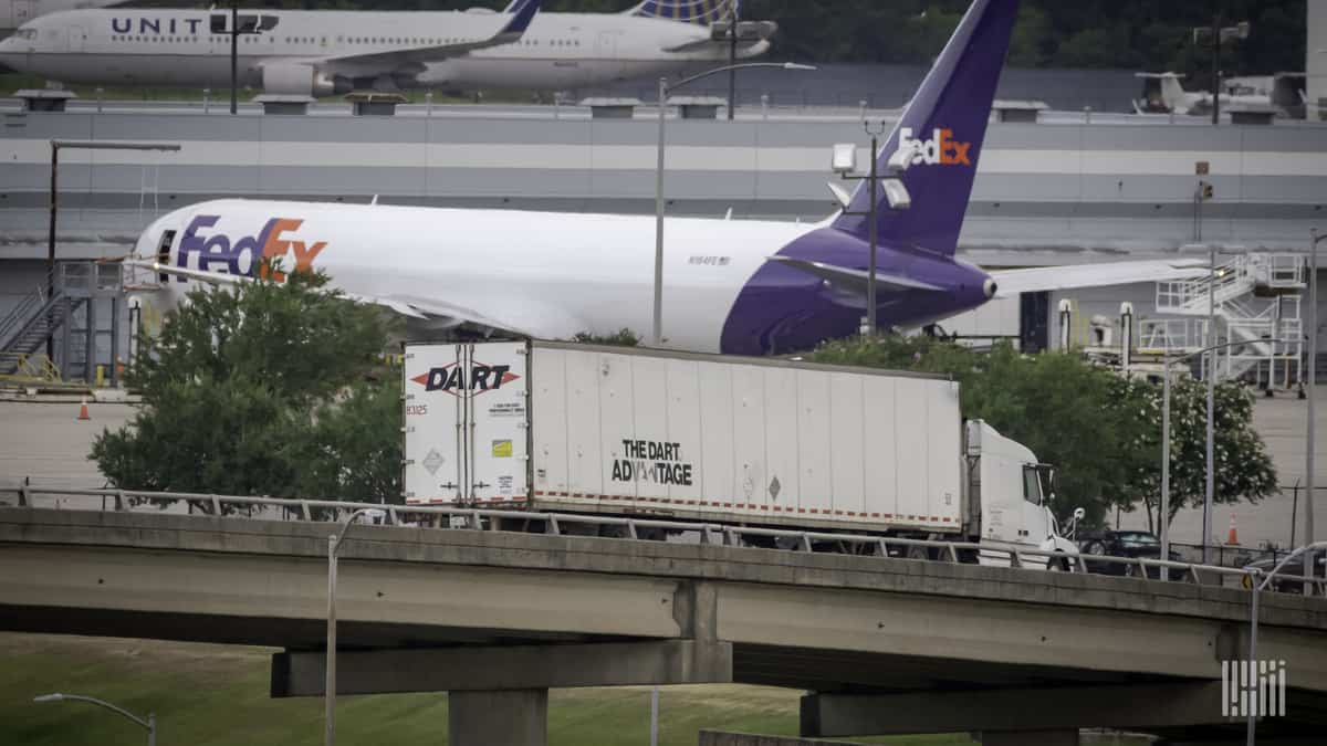 A white and purple FedEx plane on the airport apron.