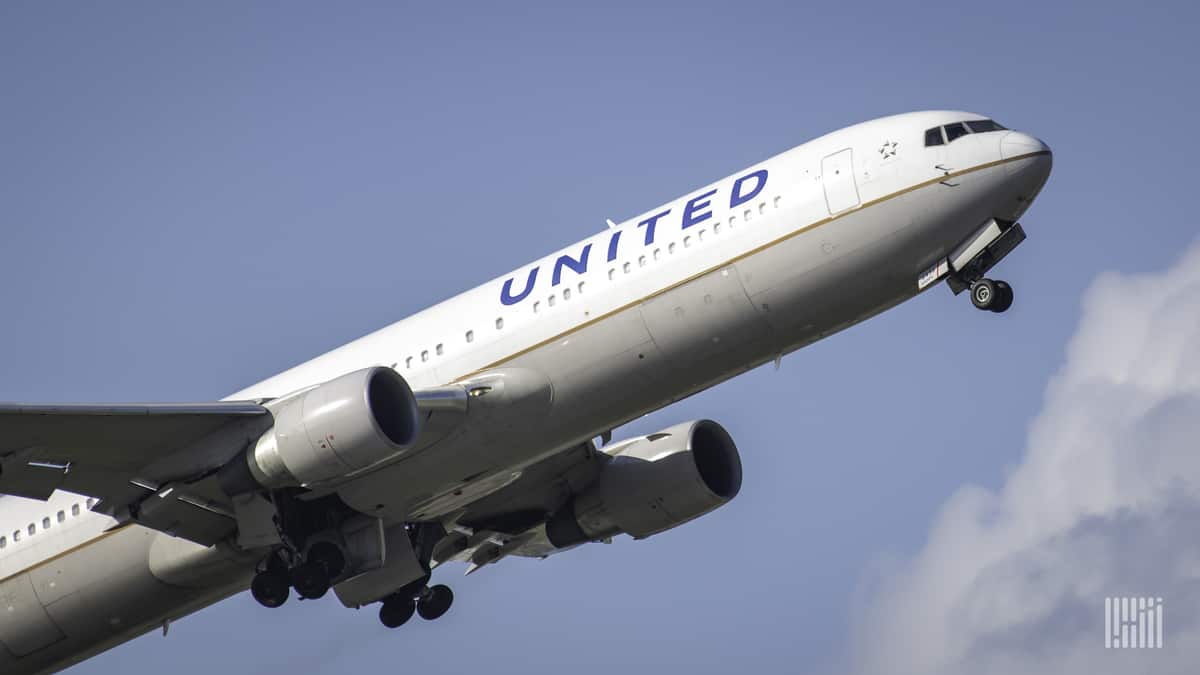 A white United Airlines plane takes off , view from behind.