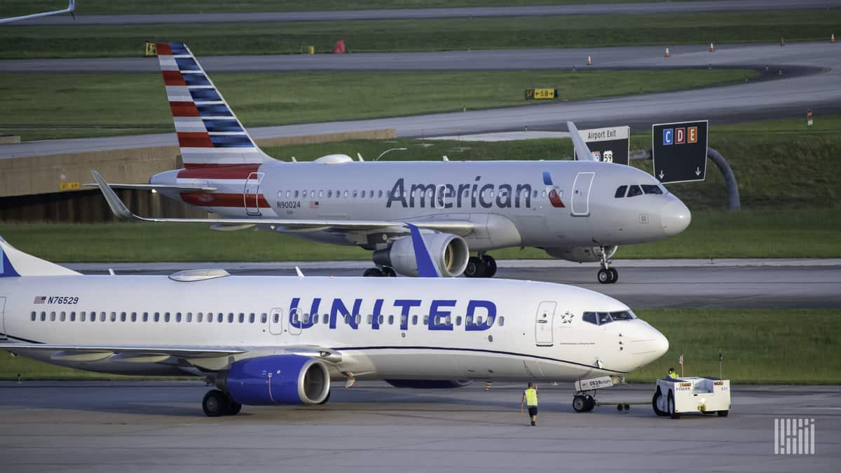 A white United Airlines jet and silver American Airlines jet on adjacent taxiways. Airlines face a financial crisis because of COVID.