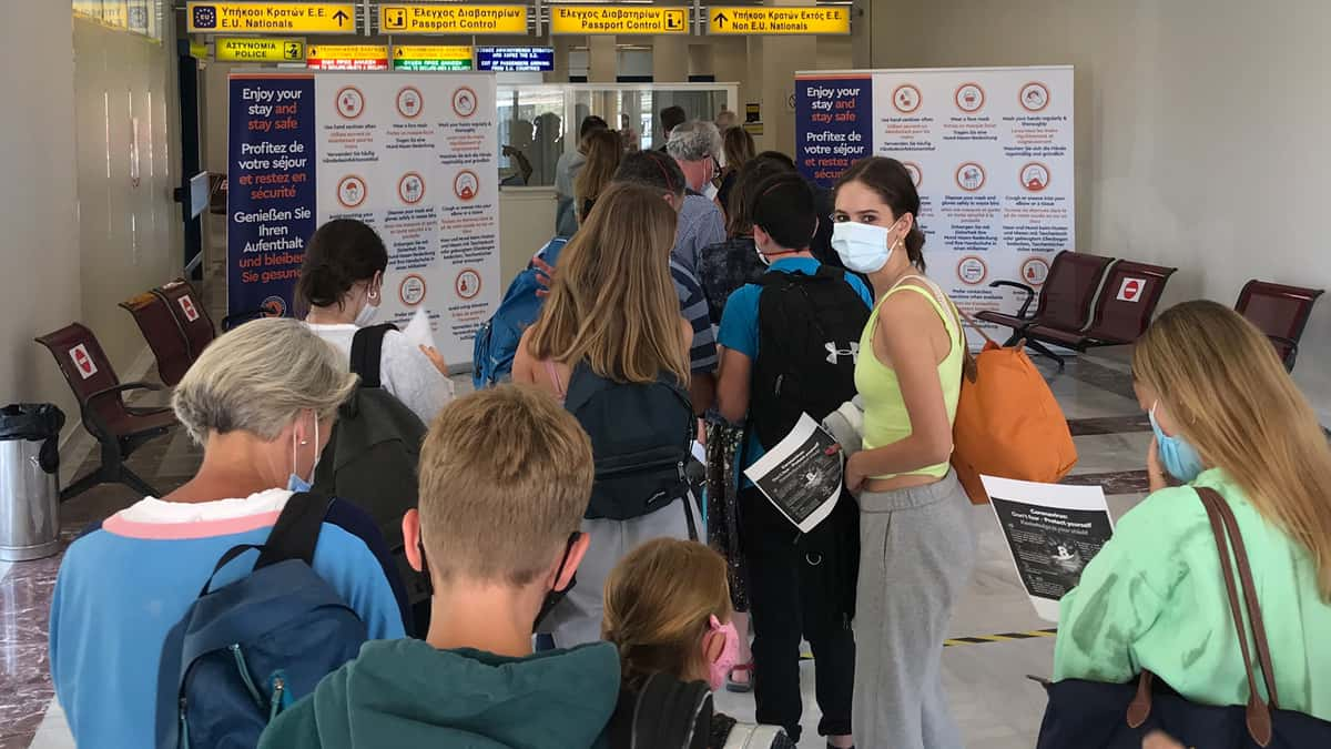 Travelers wearing masks, waiting to go through checkpoint at airport in Greece.