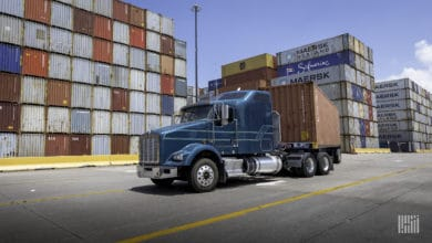 Drayage truck at port surrounded by containers