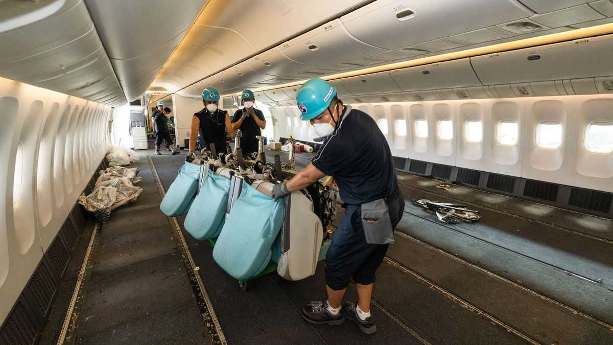 Korean Air technicians inside a jet cabin lift out the last seats to make room for floor-loading cargo.