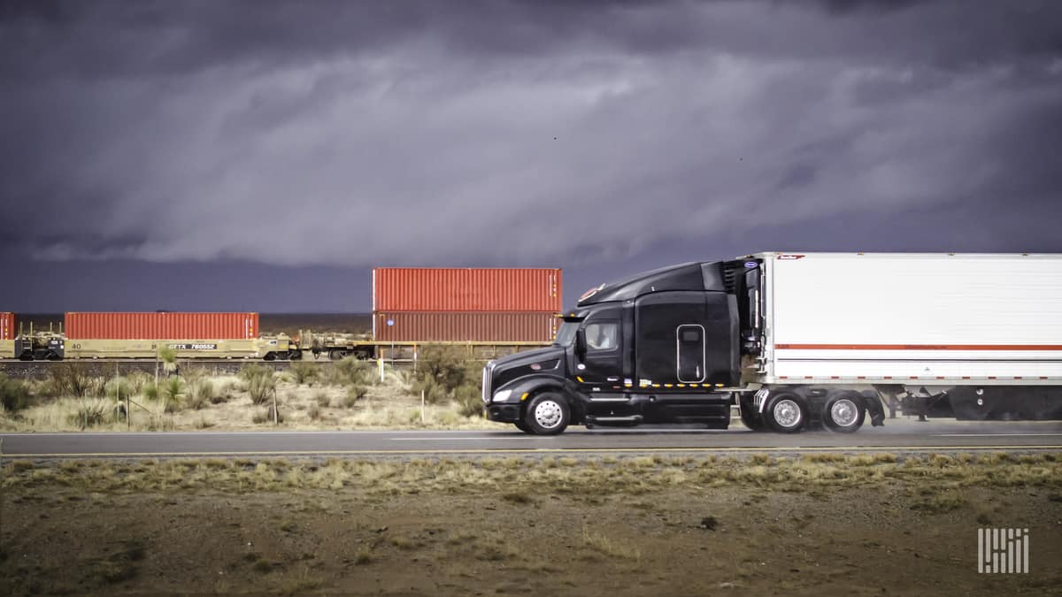 Truck on highway with intermodal train in background