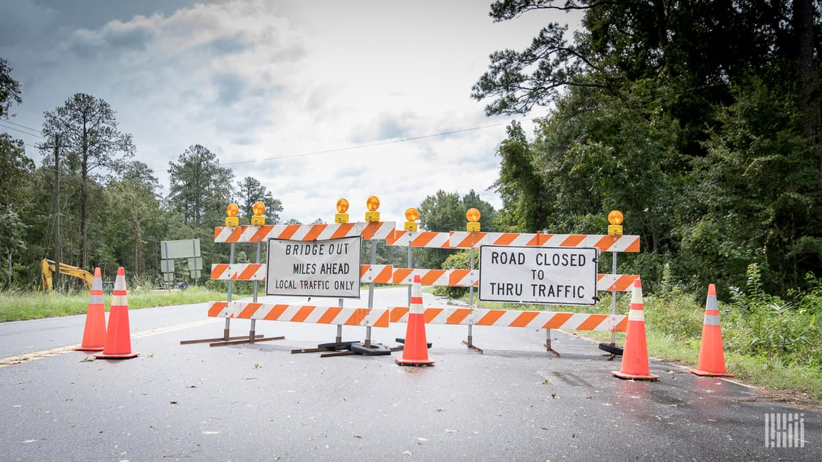 """""""Road Closed"""" barrier across a highway."""