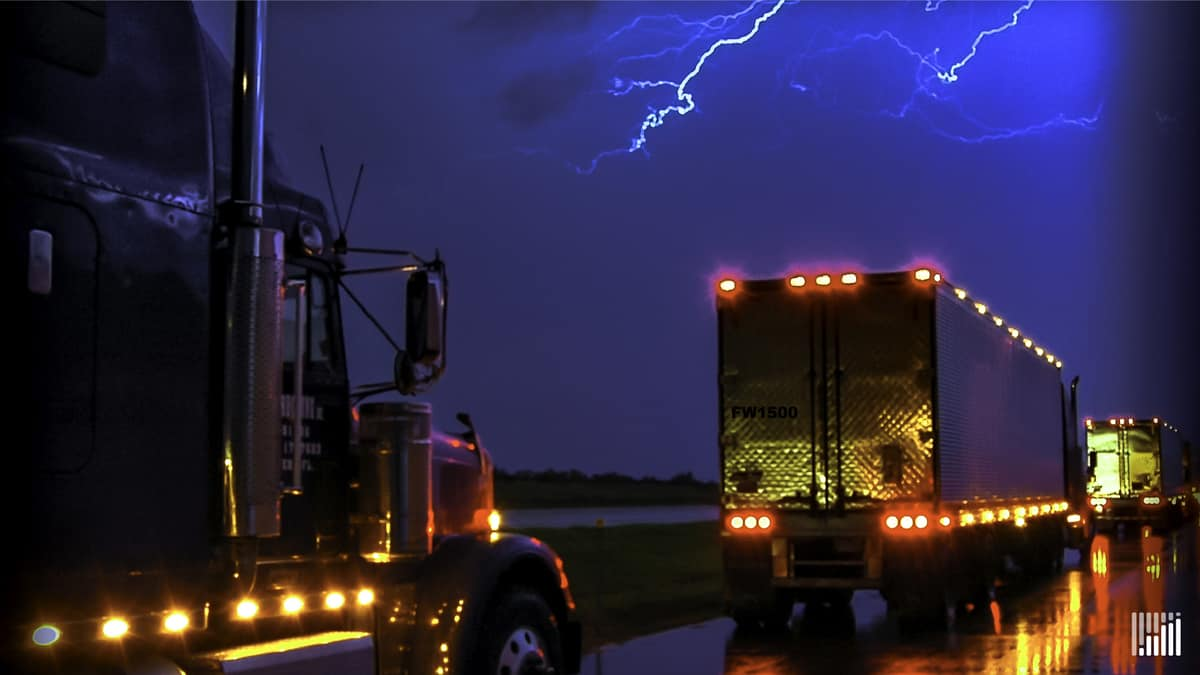 Tractor-trailers heading down highway in the rain, with lightning across the sky.