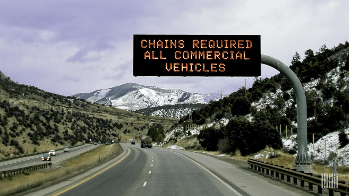 """""""Chains required"""" road sign along a snowy mountain road."""