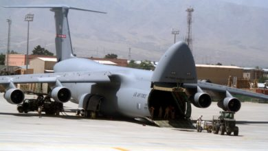 A big military cargo jet with the nose cone lifted up to allow vehicles to drive onboard. The U.S. Air Force has many C-5 cargo planes.