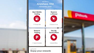 Close-up of phone with driver app in front of Pilot gas station