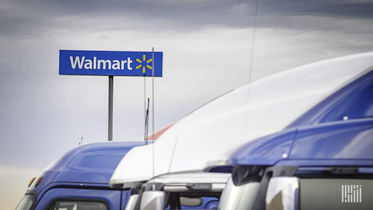 Trucks in front of a Walmart facility. Walmart Canada says a blockchain payment platform had dramatically reduced invoice disputes.