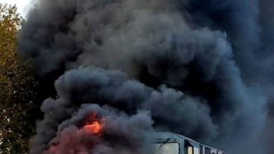 Truck on fire after train slams into it.