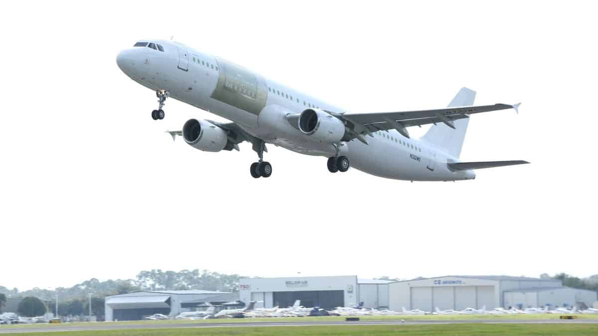 A plain white jet with a new cargo door frame visible takes off on first test flight. It's an Airbus A321 converted freighter.