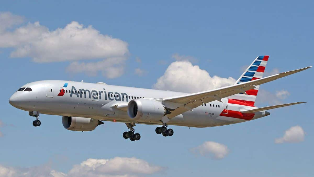 A light gray American Airlines jet comes in for landing on sunny day with wheels down.