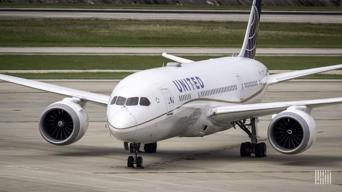 A white United Airlines jet turning on the taxiway at airport.