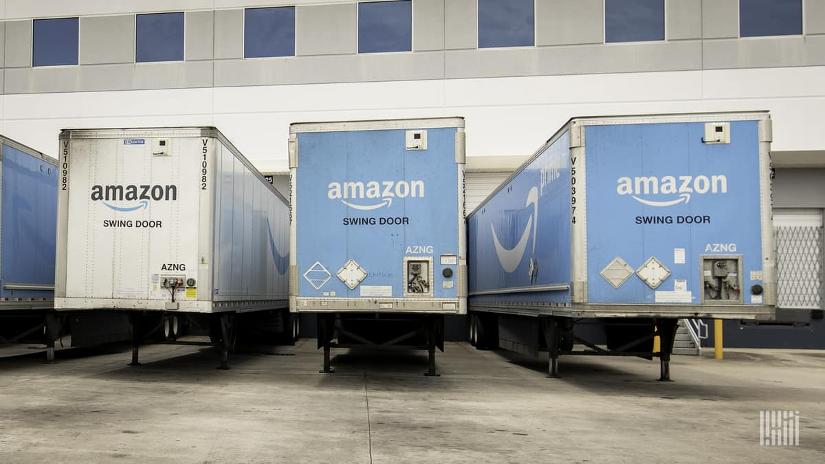 Blue Amazon truck trailers backed up to warehouse dock door waiting for a tractor to haul them away.