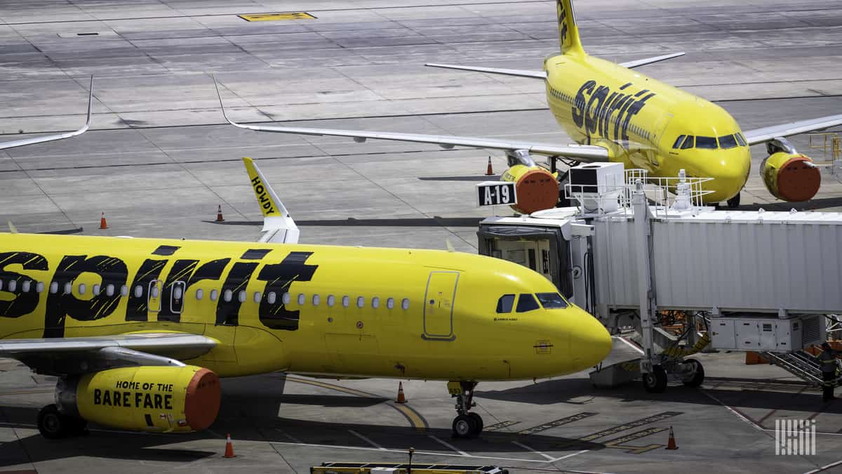 Yellow planes from Spirit Airlines parked at airport with engine covers because they are not being operated.