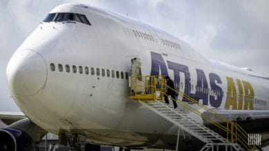 A white Atlas Air jumbo jet, with man walking up stairs into side door.