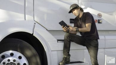 Driver leaning on his truck while using his tablet.